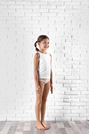 Foto de Cute little girl in underwear near white brick wall - Imagen libre de derechos