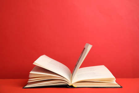 Photo for Open old hardcover book on red background. Space for text - Royalty Free Image