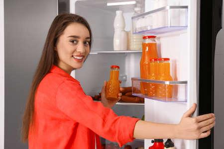 Photo pour Young woman taking juice out of refrigerator - image libre de droit