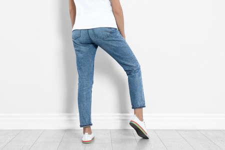 Photo pour Young woman in stylish jeans near light wall, closeup - image libre de droit