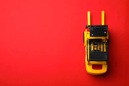 Top view of toy forklift on red background, space for text. Logistics and wholesale concept