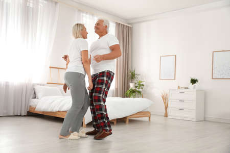 Photo for Happy mature couple dancing together in bedroom - Royalty Free Image