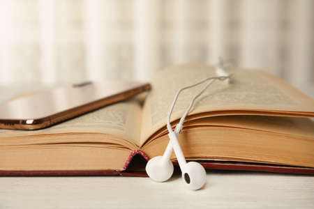 Photo for Open book, earphones and mobile phone on white wooden table, closeup - Royalty Free Image