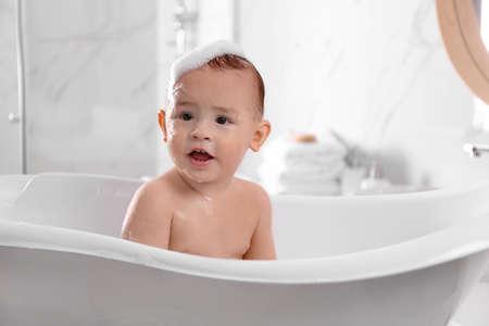 Photo pour Cute little baby in bathtub at home - image libre de droit