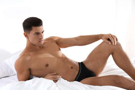 Photo pour Handsome man in black underwear on bed indoors - image libre de droit