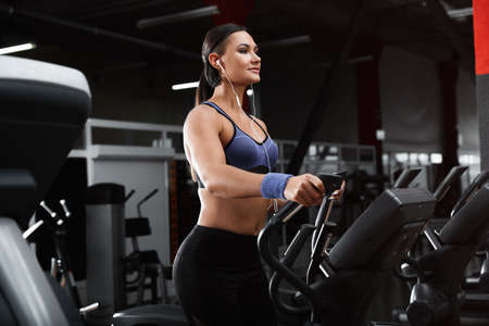 Photo pour Young woman working out on elliptical trainer in modern gym - image libre de droit