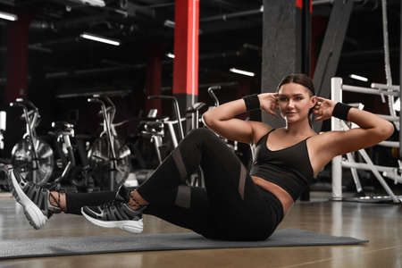 Photo for Young woman doing abdominal exercise in modern gym - Royalty Free Image