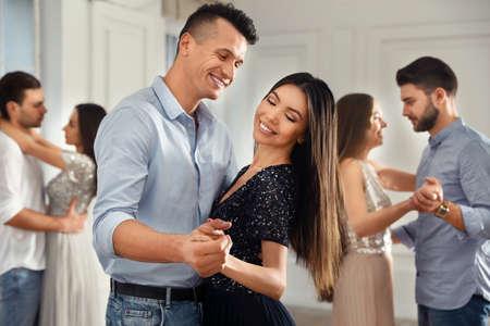 Photo pour Lovely young couple dancing together at party - image libre de droit