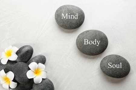 Photo pour Stones with words MIND, BODY, SOUL and flowers on light background, flat lay. Zen lifestyle - image libre de droit