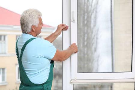 Photo pour Mature construction worker repairing plastic window indoors - image libre de droit