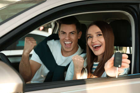 Photo for Happy couple with car key sitting in modern auto at dealership - Royalty Free Image