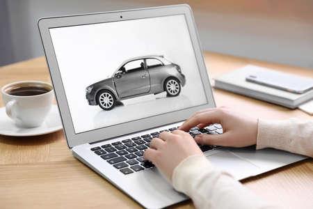 Photo pour Woman using laptop to buy car at wooden table indoors, closeup - image libre de droit