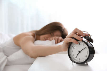 Photo pour Young woman turning off alarm clock at home in morning, focus on hand - image libre de droit