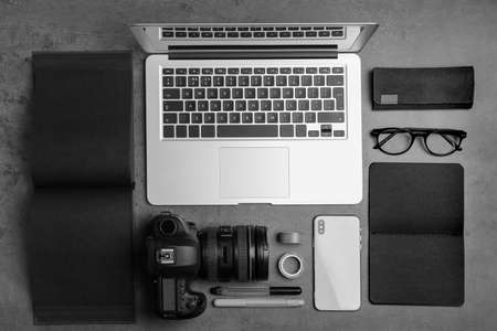 Photo for Flat lay composition with laptop, camera and smartphone on grey stone table. Designer's workplace - Royalty Free Image
