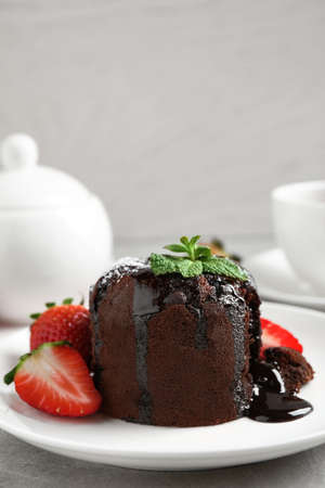 Photo for Delicious warm chocolate lava cake with mint and strawberries on table. Space for text - Royalty Free Image