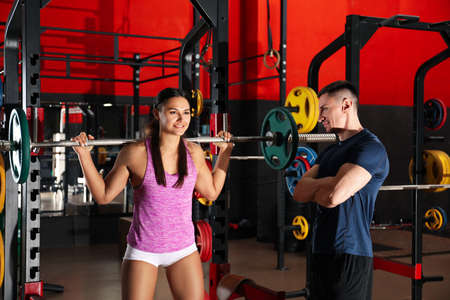Photo for Trainer and young woman working out with barbell in gym - Royalty Free Image