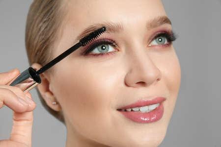 Photo pour Beautiful woman applying mascara on light grey background. Stylish makeup - image libre de droit
