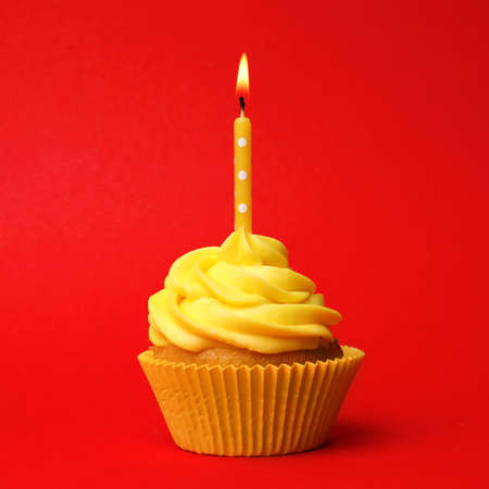 Photo pour Delicious birthday cupcake with yellow cream and burning candle on red background - image libre de droit