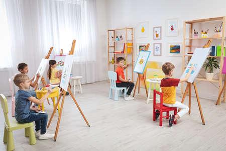 Photo pour Cute little children painting during lesson in room - image libre de droit