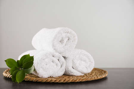Photo pour Clean rolled bath towels, green branch and wicker mat on dark grey table - image libre de droit