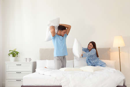 Foto de Happy couple having pillow fight in bedroom - Imagen libre de derechos