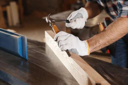 Photo pour Professional carpenter working with wooden plank in workshop, closeup - image libre de droit