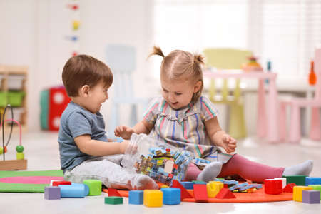 Photo pour Cute little children playing together on floor at home - image libre de droit