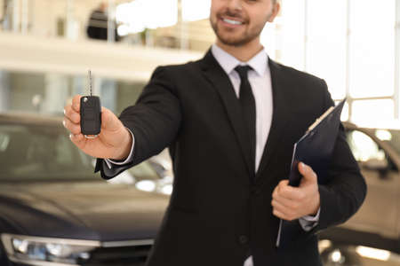 Photo pour Salesman with key and clipboard in car salon, closeup - image libre de droit