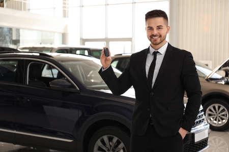 Photo pour Salesman with key in modern car salon - image libre de droit