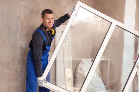 Photo pour Worker in uniform with plastic window indoors - image libre de droit