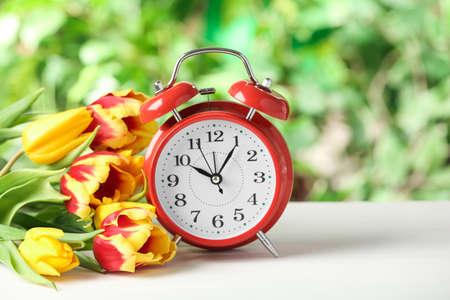 Photo pour Alarm clock and spring flowers on white wooden table. Time change concept - image libre de droit