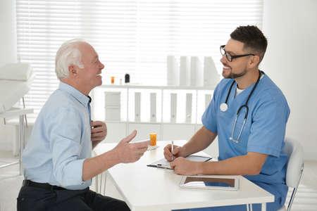Photo pour Doctor examining senior patient in modern office - image libre de droit