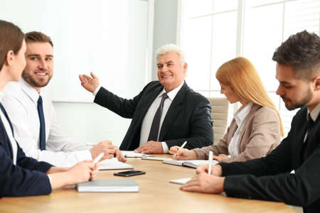 Photo for Senior business trainer working with people in office - Royalty Free Image