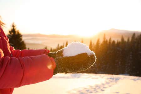 Photo pour Woman holding pile of snow outdoors, closeup. Winter vacation - image libre de droit