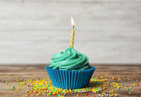 Photo pour Delicious birthday cupcake with cream and burning candle on wooden table - image libre de droit