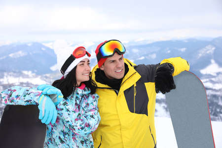 Photo pour Couple with snowboards at mountain resort. Winter vacation - image libre de droit