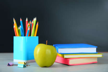 Photo pour Apple and school stationery on white wooden table. Doing homework - image libre de droit