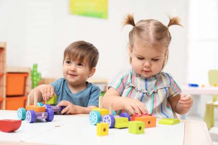 Photo pour Little children playing with construction set at table - image libre de droit