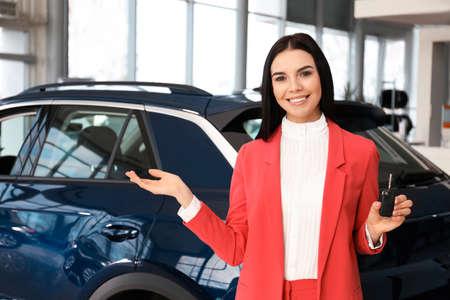 Photo pour Saleswoman with key near car in dealership - image libre de droit