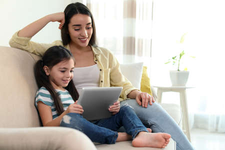 Photo pour Mother and daughter reading E-book together at home - image libre de droit