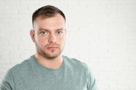 Photo pour Portrait of young man near white brick wall. Space for text - image libre de droit