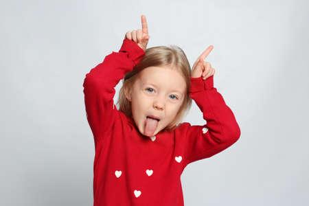 Photo pour Portrait of cute funny little girl on light grey background - image libre de droit