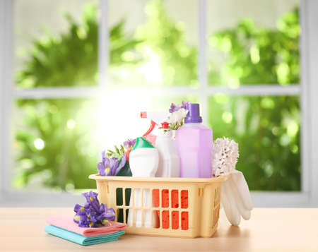 Photo pour Plastic basket with different detergents on wooden table indoors. Spring cleaning concept - image libre de droit