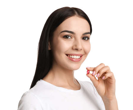 Photo for Young woman with vitamin capsule on white background - Royalty Free Image