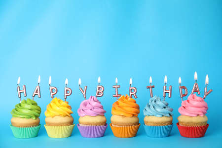 Photo pour Birthday cupcakes with burning candles on blue background. Space for text - image libre de droit