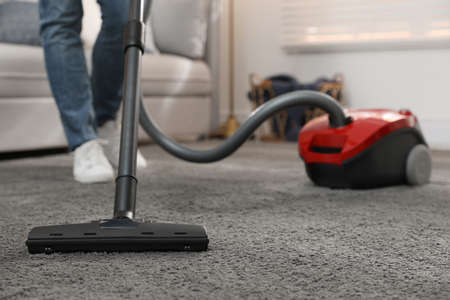 Photo for Young man using vacuum cleaner at home, closeup - Royalty Free Image