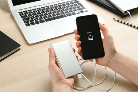 Photo for Woman charging mobile phone with power bank at wooden table, closeup - Royalty Free Image