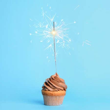 Photo pour Birthday cupcake with sparkler on light blue background - image libre de droit