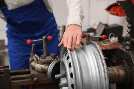 Photo pour Mechanic working with car disk lathe machine at tire service, closeup - image libre de droit