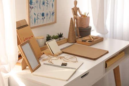 Foto de Wooden human figure and stationery on white table indoors. Interior elements - Imagen libre de derechos